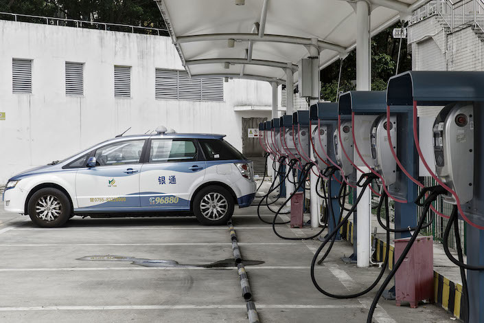 A BYD E6 electric taxi is charged at the company's charging station in Shenzhen. Photo: Bloomberg