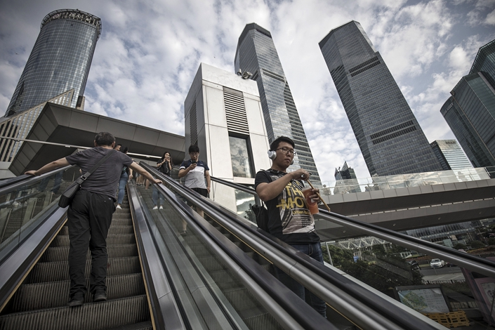 Pedestrians ride an escalator in the Lujiazui Financial District in Shanghai on Sept. 4, 2017. Photo: Bloomberg