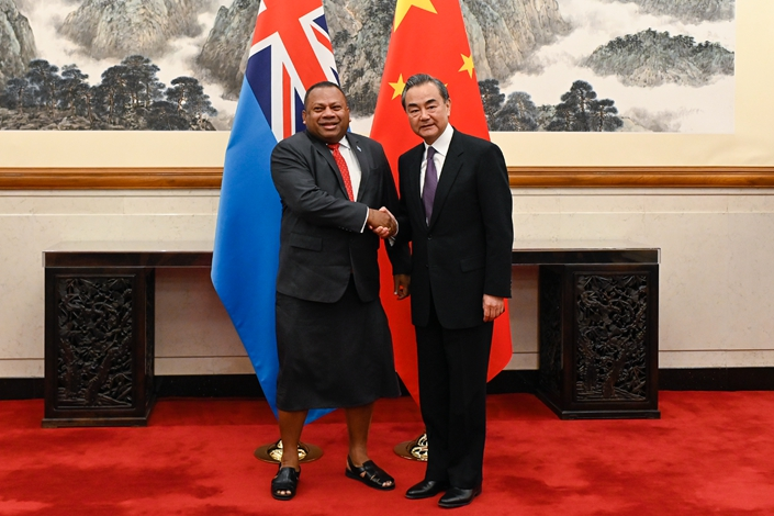 Chinese Foreign Minister Wang Yi, right, shakes hands with Fiji's Minister for Foreign Affairs Inia Seruiratu before their meeting at the Diaoyutai State Guesthouse on June 11 in Beijing. Photo: IC Photo