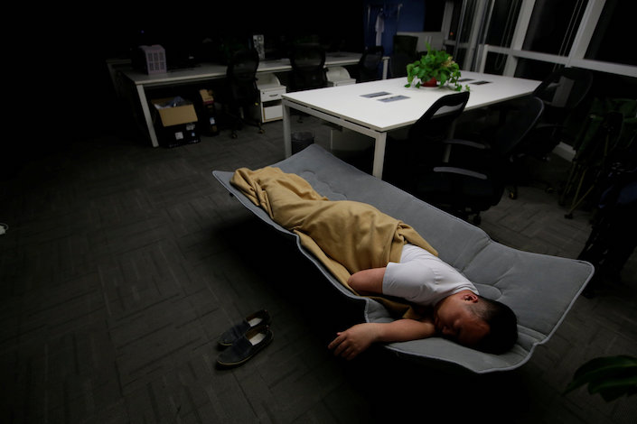 An Internet engineer sleeps on a camp bed at his office after finishing work early morning. Photo: VCG
