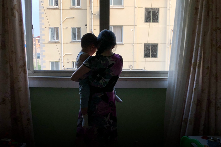 Zou Xiaoqi holds her son at her home in Shanghai on July 20. Photo: Fu Danni/Sixth Tone