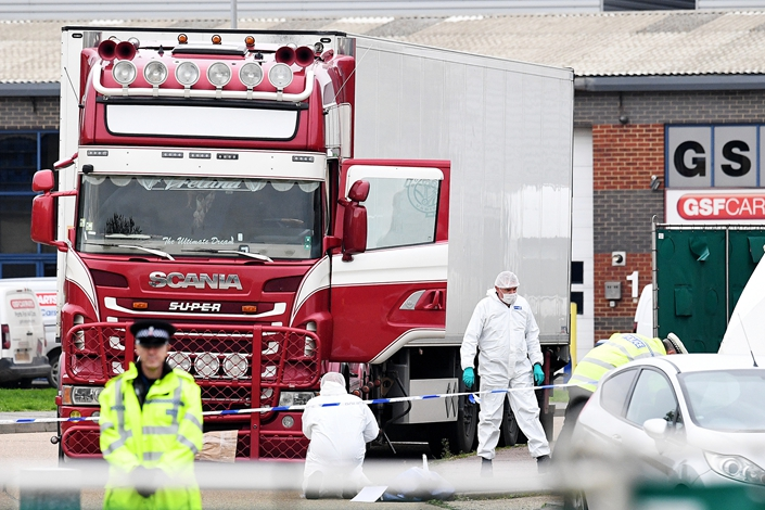 Police and forensic officers investigate a truck in which 39 bodies were discovered in the trailer, as they prepare move the vehicle from the site on Wednesday in Thurrock, England. Photo: VCG