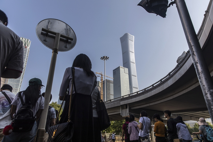 Pedestrians wait to cross a road near Beijing's central business district on Sept. 26. Photo: Bloomberg