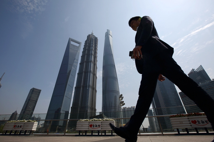 A man walks in Shanghai's Lujiazui district on April 23, 2015. Photo: Bloomberg