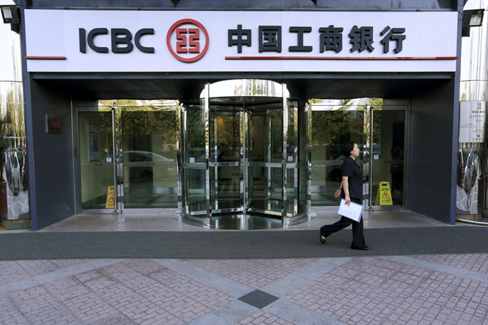 A woman walks past a branch of the Industrial & Commercial Bank of China (ICBC) in Beijing on Aug. 22, 2012. Photo: Bloomberg
