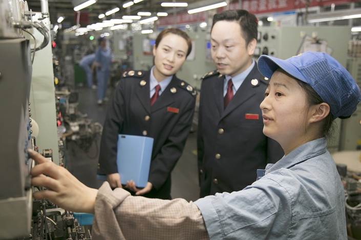 A State Administration of Taxation official promotes the new national tax and fee reduction policy on April 10 at a company in Yichun, East China's Jiangxi province. Photo: VCG