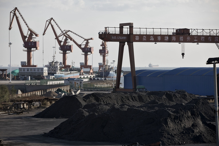 Pies of coal sit near the port facilities in Qinhuangdao, Hebei province, on Oct. 28, 2016. Photo: Bloomberg