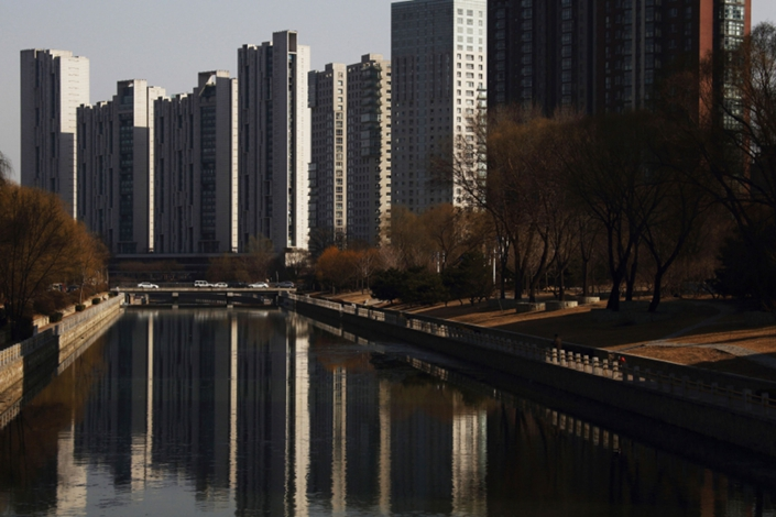 Residential towers are reflected in a river in Beijing  on  March 10, 2015. Photo: Bloomberg