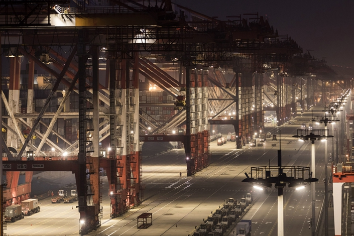 Gantry cranes and trucks move on the docks during early morning at Yangshan Deepwater Port in Shanghai, on Aug. 7, 2019. Photo: Bloomberg