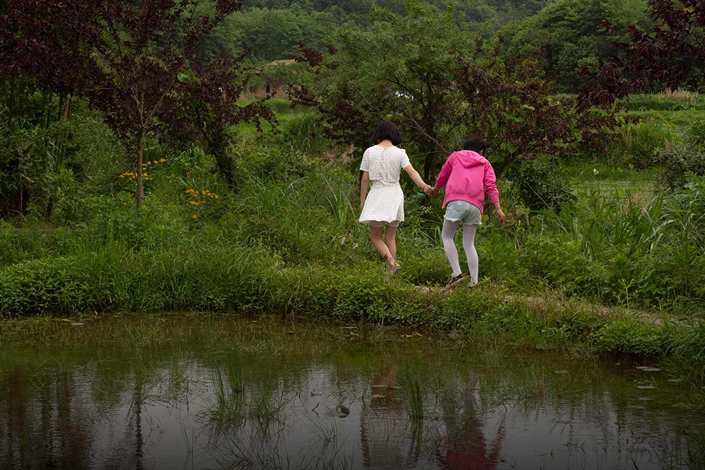 Two girls walk through a field in Jinkeng, East China's Jiangxi province, April 26. Photo: Shi Yangkun/Sixth Tone