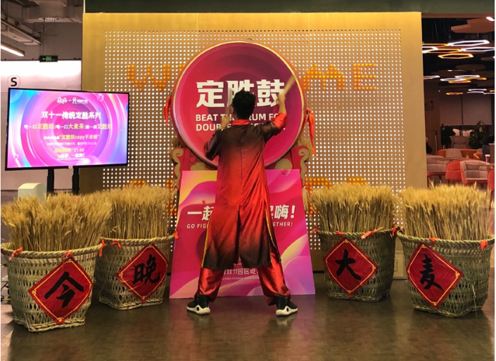 An Alibaba staffer beats a 'Victory Drum' surrounded by baskets of barley at the e-commerce company's campus in Hangzhou, Zhejiang province, Nov. 11, 2019. Photo: Zhao Runhua/Caixin