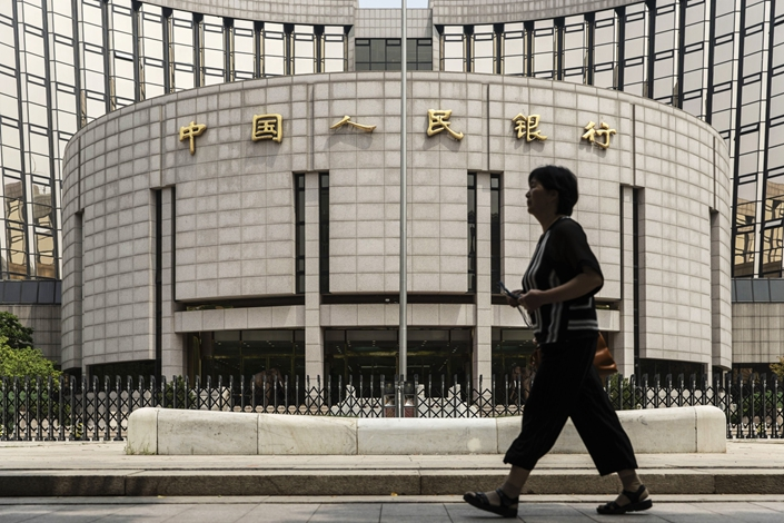 A woman walks past the People's Bank of China (PBOC) in Beijing
