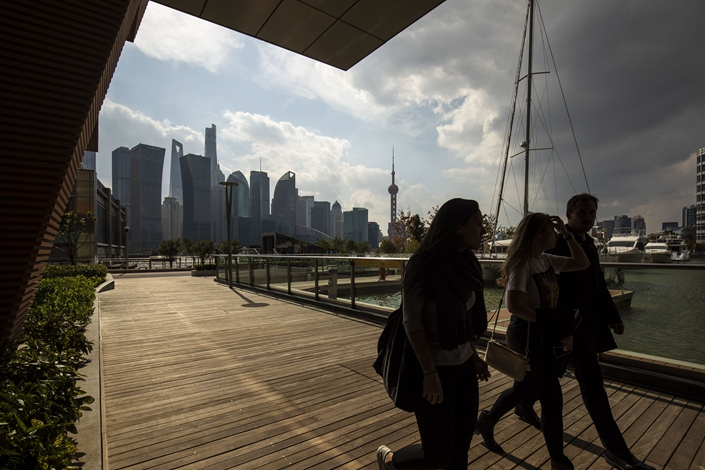 People enjoy the sunshine while standing on an area collectively known as the North Bund, with the skyscrapers of the Pudong Lujiazui Financial District across the Huangpu River in Shanghai on Nov. 13, 2018. Photo: Bloomberg