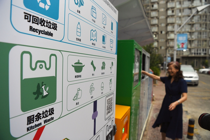 A grinning lady deposits trash into a garbage sorting station at a residential development in Beijing on July 5. Photo VCG