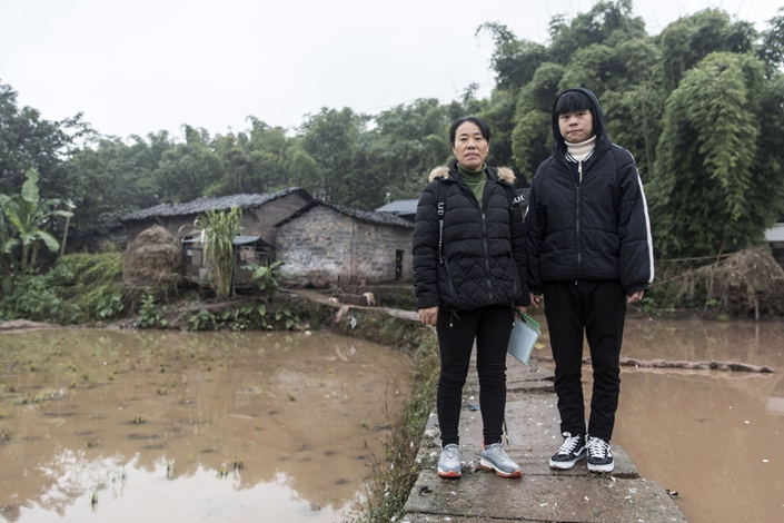 Zhang Haitao and his aunt Chen Chunhua have their photos taken while standing in front of their home in Wushi village near Guang'an, Sichuan province, on Nov. 28. Photo: Bloomberg