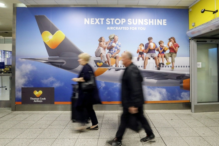 Passengers walk past an advertisement for Thomas Cook Group Plc at the South Terminal of London Gatwick Airport near Crawley