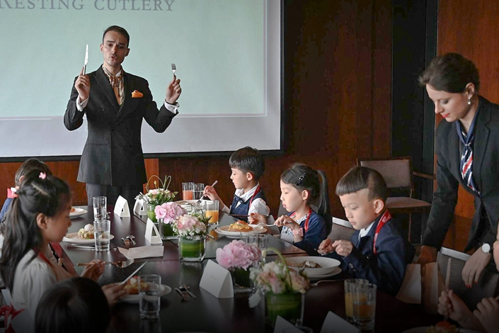 Guillaume de Bernadac teaches children how to use cutlery during an etiquette and manners lesson in central Shanghai, June 1. Photo: Hector Retamal/AFP/VCG