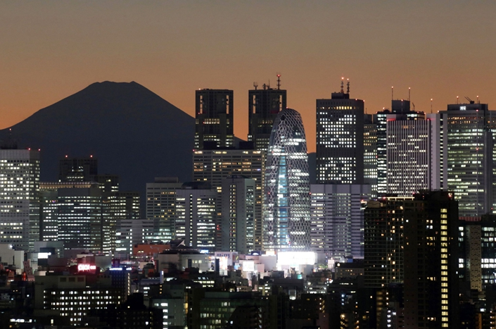 The sun sets behind buildings in front of Mount Fuji at dusk in Tokyo, Japan, on Dec. 12, 2013. Photo: Bloomberg