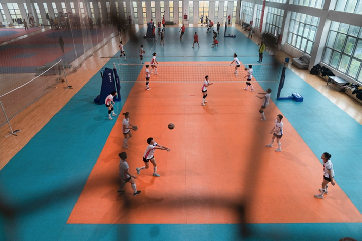 Female students attend volleyball training at Zhoukou City Sports School in Zhoukou, Henan province, in early December. The school's boys' taekwondo team practices in the background.
