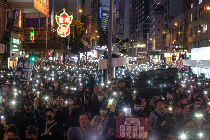 Demonstrators hold signs during a protest in Hong Kong on Dec. 8. Photo: Bloomberg