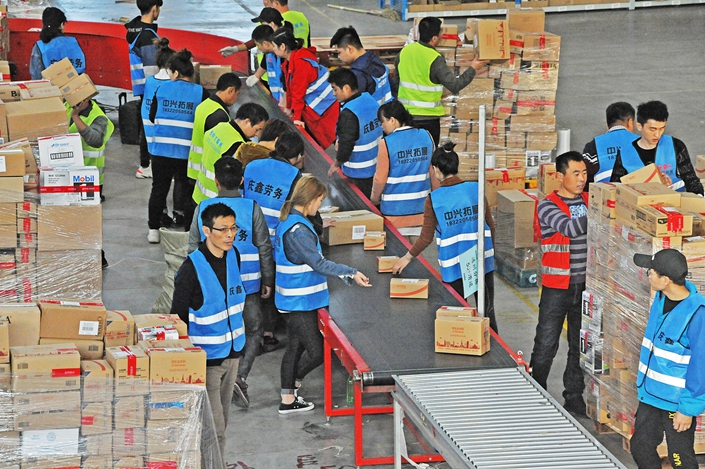 Workers sort packages of imported goods on Nov. 11 at JD.com's cross-border e-commerce warehouse in the northern city of Tianjin.