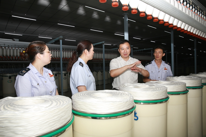An official discusses taxation at a textiles factory in Nantong, Jiangsu province, on July 19.