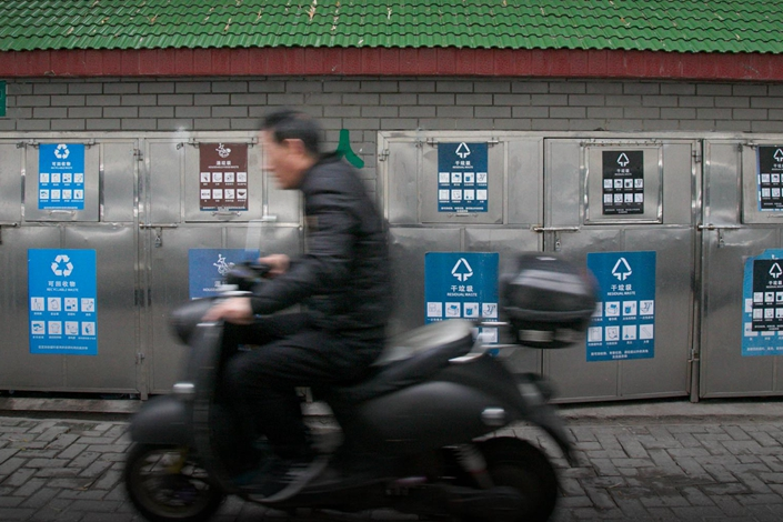 A man rides past a waste-disposal area in Shanghai, Dec. 26. Photo: Sixth Tone