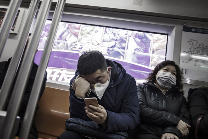 Passengers wearing face masks ride the subway in Beijing in January 2017. Photo: Bloomberg