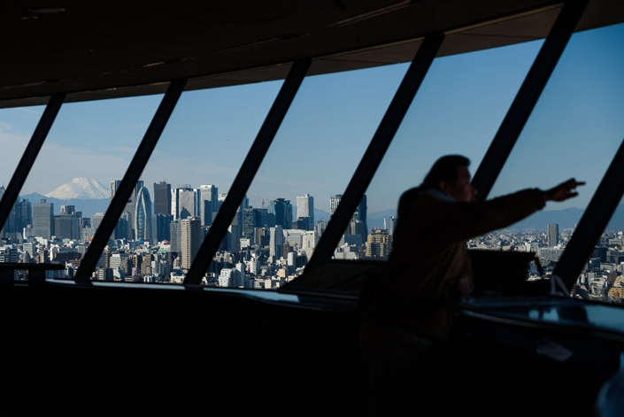 Mount Fuji stands behind buildings as a visitor looks out at the skyline from an observation deck in Tokyo