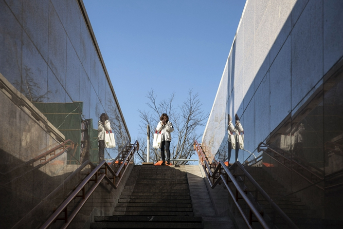 A woman looks at her phone while entering a pedestrian underpass in Beijing on Feb. 15. Photo: Bloomberg