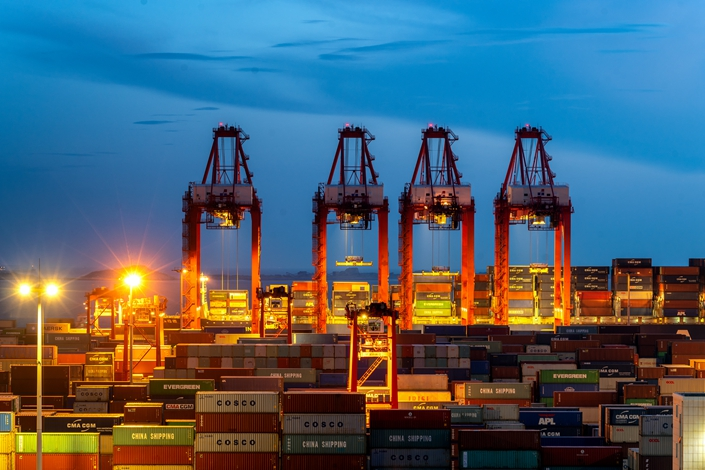 Cranes lift cargo containers at a terminal at the port of Yangshan in Shanghai
