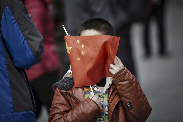 A boy wraps his face with a Chinese national flag while standing on Tiananmen Square in March 2017. Photo: Bloomberg