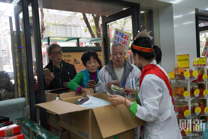 Customers endure long lines to buy protective face masks on Tuesday outside a pharmacy in Guangzhou, South China's Guangdong province. Photo: Liang Yingfei/Caixin