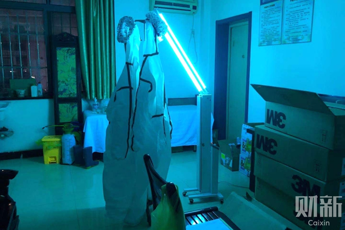 A community clinic in Wuhan sterilizes its sole hazmat suit with ultraviolet light for reuse. Photo: Xiao Hui/Caixin