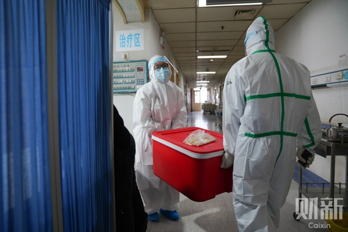 Medical workers carry supplies in Wuhan, Hubei province, on Jan. 24. Photo: Ding Gang/Caixin