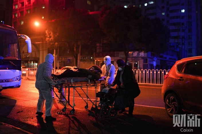 Medical staff use a stretcher to move a patient in front of the Wuhan No. 7 Hospital on Feb. 2. Photo: Ding Gang/Caixin