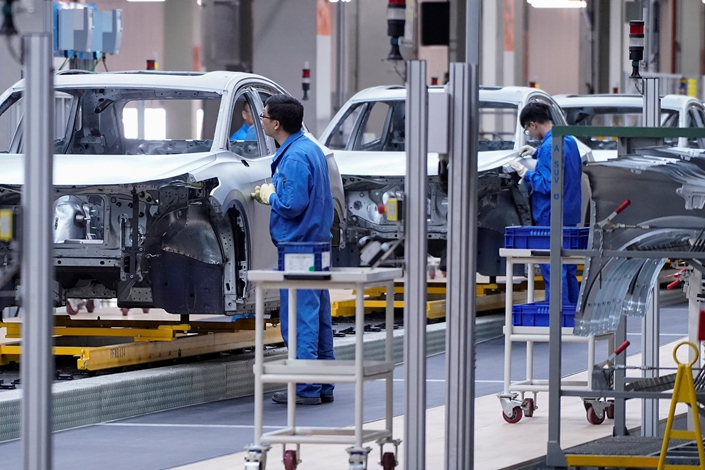 Employees work on assembly line at a SAIC Volkswagen electric vehicle plant in Shanghai. Photo: VCG