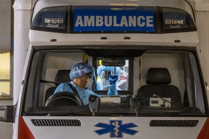 Emergency medical technicians in protective gear speak onboard an ambulance outside Queen Mary Hospital in Hong Kong on Wednesday. Photo: Bloomberg