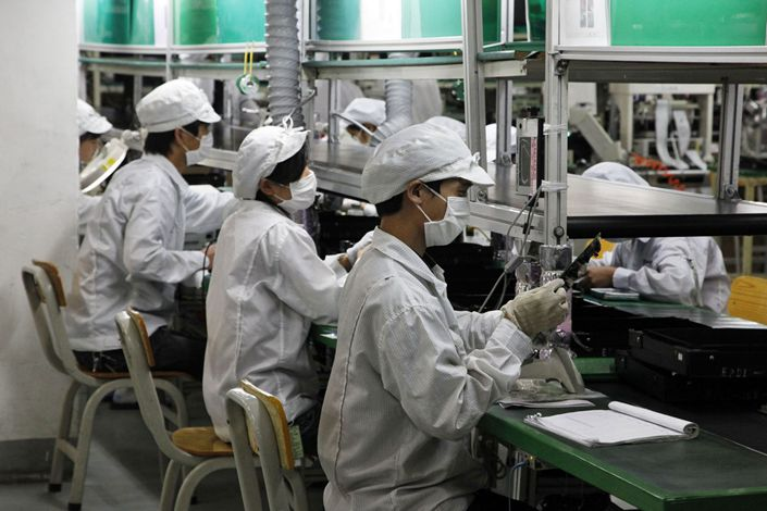 Foxconn employees operate on the assembly line at a Hon Hai factory in Longhua, Shenzhen, on May 26, 2010. Photo: Bloomberg