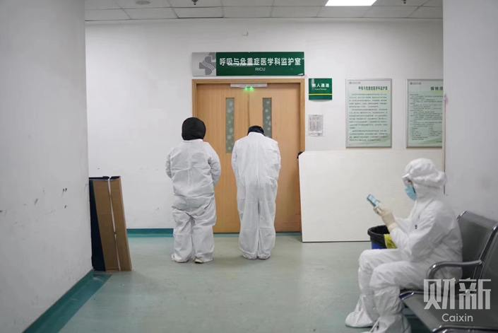 Li Wenliang's colleagues wait outside the emergency room where he was being treated. Photo: Ding Gang/Caixin