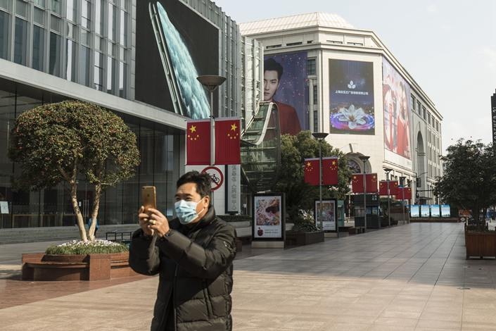 A man takes a pictures of an almost empty Nanjing Road in Shanghai on Feb. 5. Photo: Bloomberg