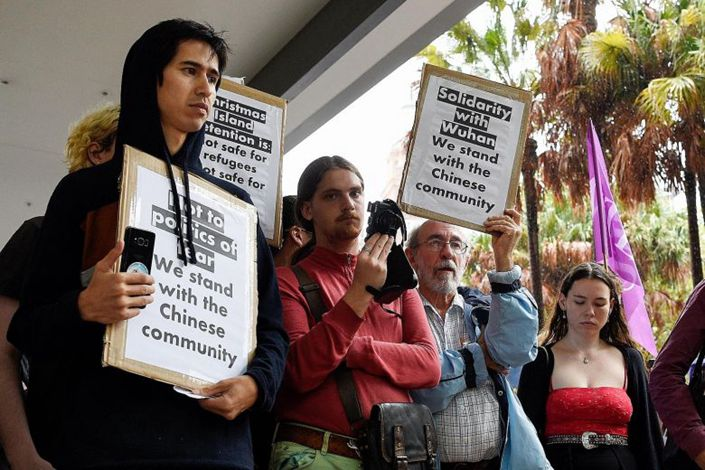 Protesters in Sydney hold placards outside Australia's Department of Immigration and Border Protection during a rally against an inbound travel ban on foreign travellers from China. PHOTO: EPA-EFE