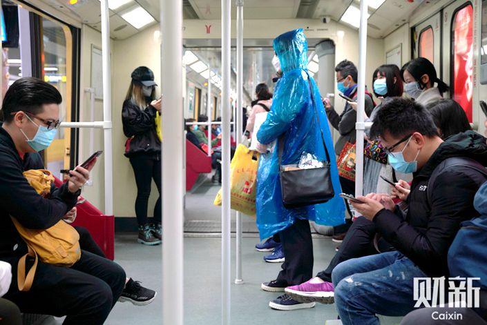 Passengers wear masks on the Guangzhou subway on Feb. 10. Photo: Liang Yingfei/Caixin