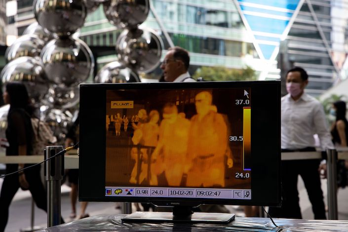 A monitor displays a thermographic image of office workers passing through a gate outside an office building in the central business district of Singapore. Photo: Bloomberg