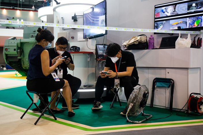 Employees wearing protective masks use smartphones during a media preview day at the Singapore Airshow held at the Changi Exhibition Centre in Singapore, on, Feb. 9. Photo: Bloomberg