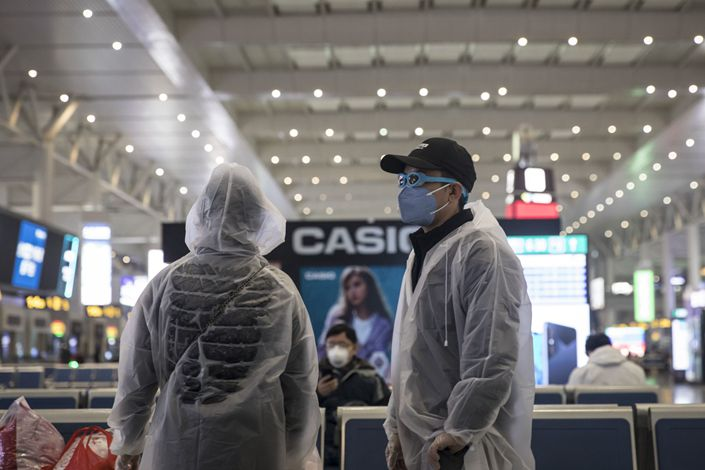 A family wearing masks and make-shift protective gear wait for their train Tuesday at the Hongqiao Railway Station in Shanghai. Photo: Bloomberg