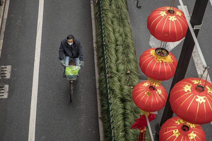 A man rides his bike past decorative lanterns Tuesday in Hangzhou, East China's Zhejiang province. Photo: Bloomberg