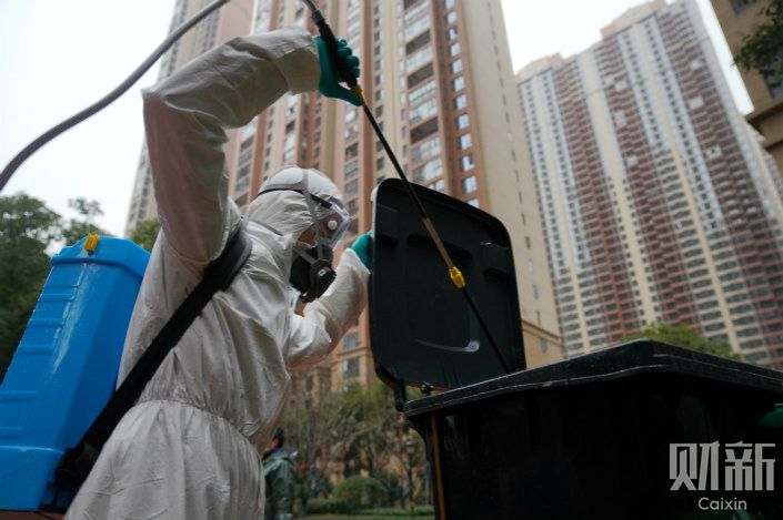 A worker disinfects a residential area Tuesday in Wuhan, capital of Central China's Hubei province. Photo: Ding Gang/Caixin