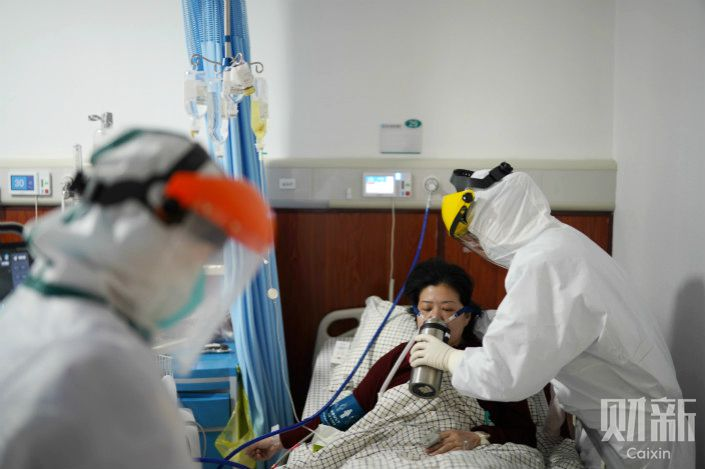 A medical worker cares for a coronavirus patient in Wuhan, Hubei province. Photo: Ding Gang/Caixin
