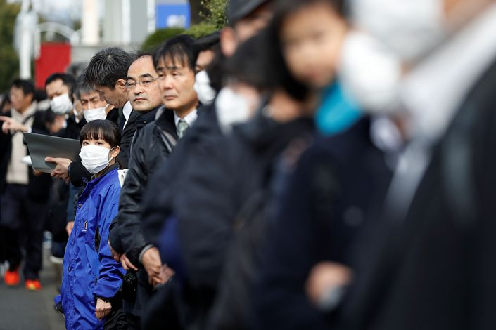 People wearing face masks wait for the start of a rehearsal of part of the Tokyo 2020 Olympic Torch Relay in Hamura, on the outskirts of Tokyo, on Feb. 15. Photo:VCG